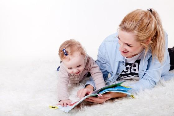 赤ちゃんと女性が寝そべって一緒に絵本を見ている