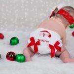四つん這いで後ろを向いている赤ちゃん パンツにはサンタさんのアップリケとリボンがついていて、周りには赤と緑のオーナメントが転がっている