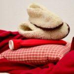 赤色の毛布と枕と湯たんぽが重なっている