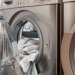 ドラム式洗濯機の扉が半分開き中からタオルが少し出ている