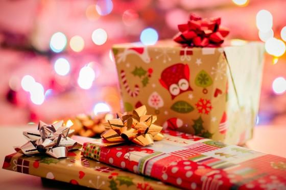 ツリーの電球を背景にクリスマスプレゼントが3つ置いてある