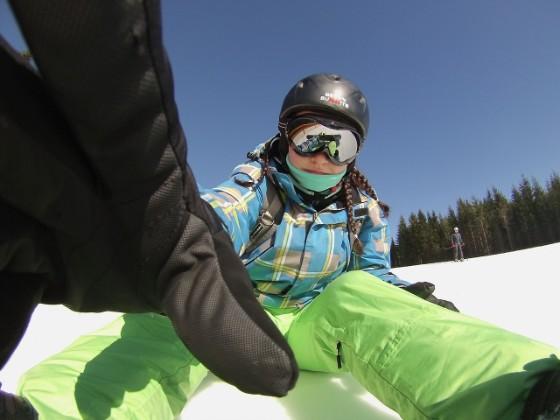 ゲレンデで雪の上に座りこちらに手を伸ばす子供