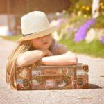 帽子をかぶった女の子が荷物のカバンに組んだ腕を置いている
