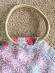 フェイスタオルの角に丸くした紐を縫い付けた