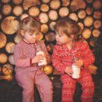 あたたかそうなパジャマを着た女の子がミルクを飲んでいる